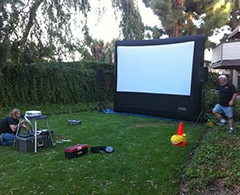 Crew sets up outdoor movie projector and inflatable screen.