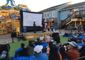 Crowd watching Forrest Gump trivia game on stage before outdoor movie at Pier 39
