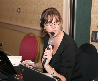 Woman working table booth with headset, laptop and wireless mic.
