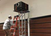 AV technician climbing ladder to install digital cinema projector