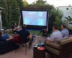 Group of guys watch outdoor movie on inflatable screen on patio.