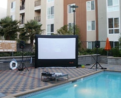 Inflatable outdoor screen, projector and sound system set up by pool.
