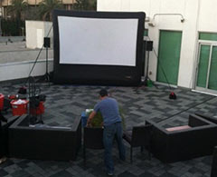 Man sets up outdoor movie viewing area with inflatable screen, sound system and projector.